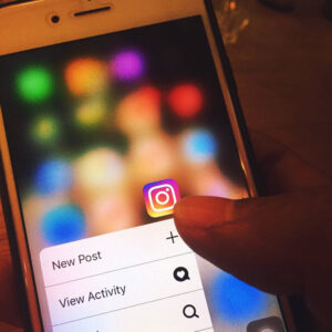 A person touches the Instagram app icon on their iPhone opening the dropdown menu