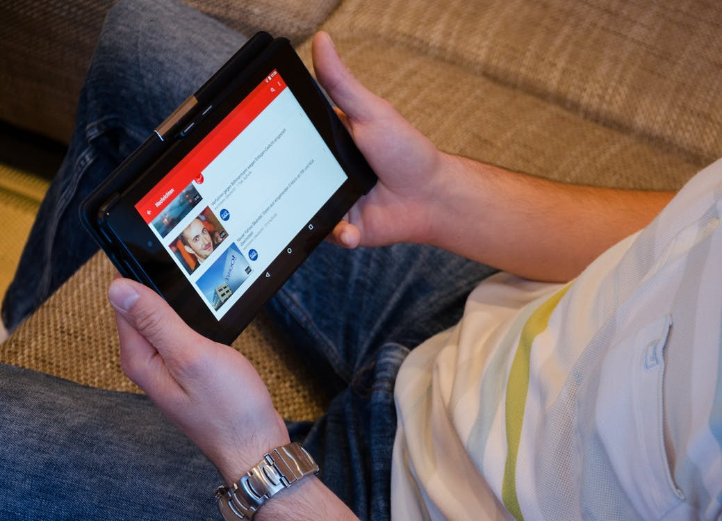 A man holding a tablet with YouTube opened on it.